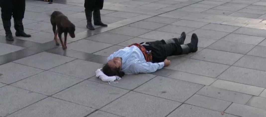 Un acteur de rue fait semblant d'être blessé quand un chien errant se promène pour le réconforter